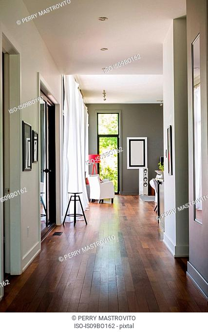 Hallway with qumaru wood floorboards leading to living room with white leather armchair, luxurious modern cube style house interior