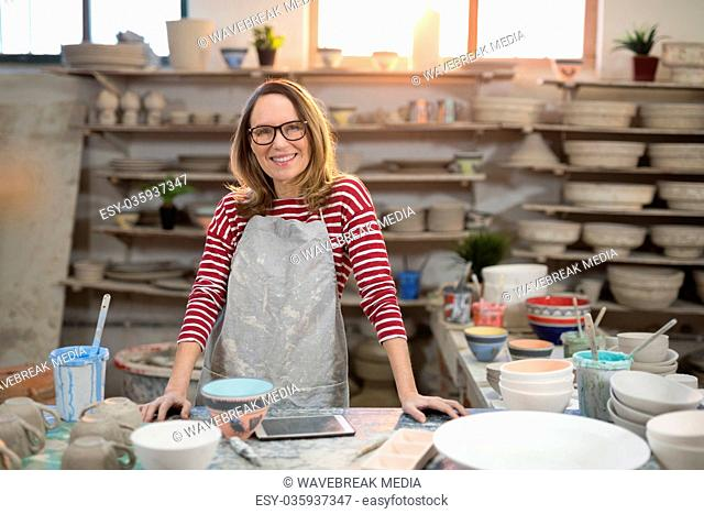 Portrait of female potter standing at worktop