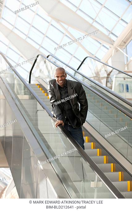 African American businessman smiling on escalator