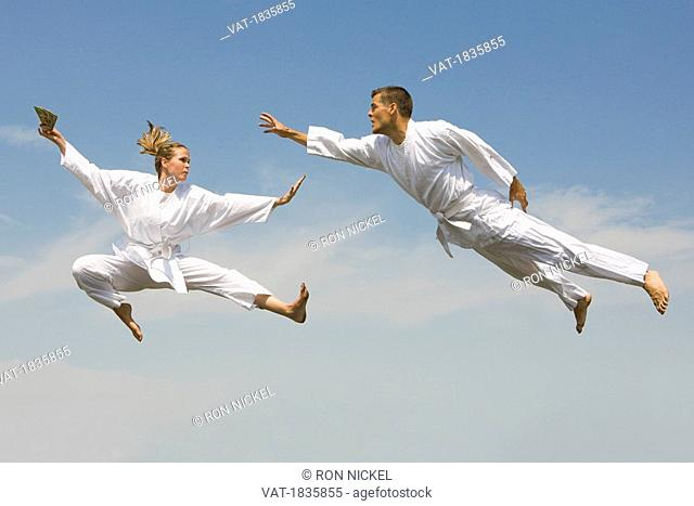 Young woman holding cash evading young man as they fly through the air