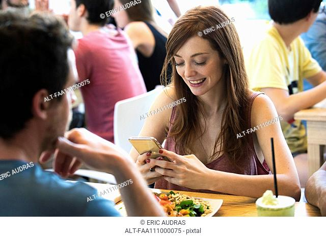 Woman using smartphone in restaurant