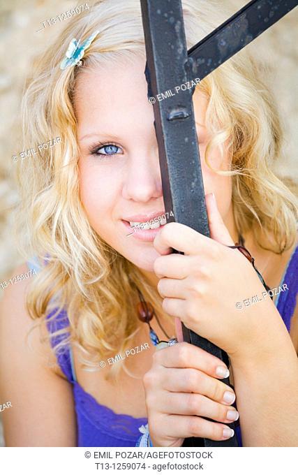 Peeking behind iron bar shy teen girl