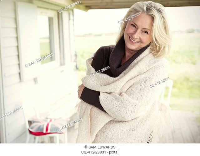 Portrait smiling senior woman wearing shawl on porch