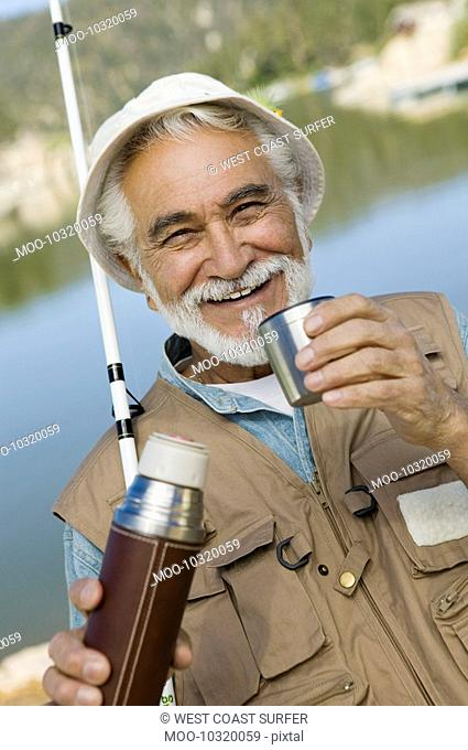 Middle-aged man fishing holding vacuum flask smiling portrait