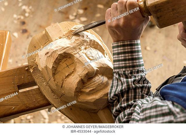 Carving the face of a wooden mask into wooden block using wood carving tools, wooden mask carver, Bad Aussee, Styria, Austria