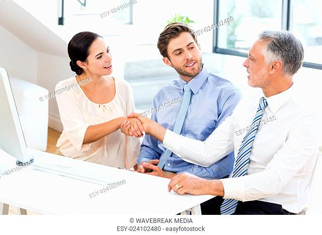 Businessman shaking hands with businesswoman in meeting