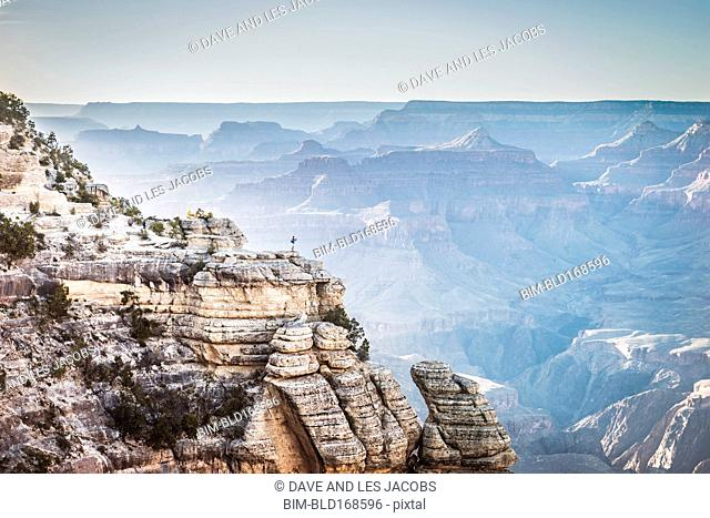 Distant Caucasian man at edge of canyon, Grand Canyon, Arizona, United States