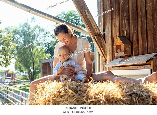 Happy mother and little daughter sitting in straw in a barn