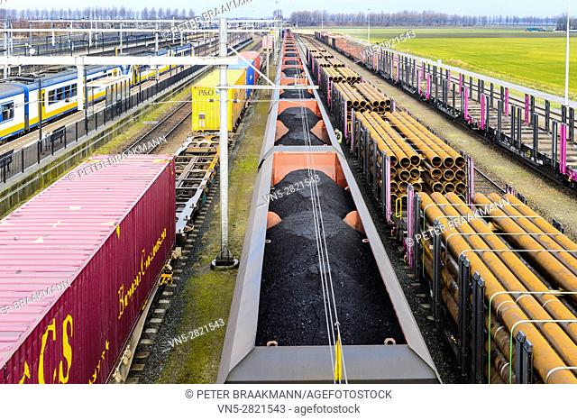"""LAGE ZWALUWE, THE NETHERLANDS â. """" JANUARY 29: Passenger Train, train loaded train with coal and steel tubes on station on January 29, 2017"""