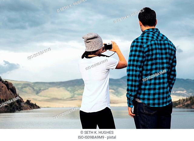 Couple beside Dillon Reservoir, taking photograph, rear view, Silverthorne, Colorado, USA