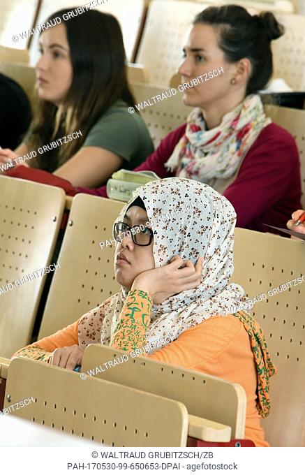 Disabled student Vanqia Tambunan from Indonesia (front) follows the lecture 'Introduction to the marekts of the agricultural and nutritional economy' at the...