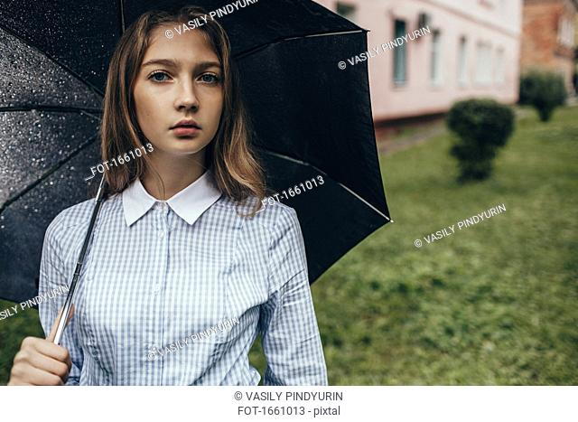 Portrait of teenage girl holding umbrella on grassy field