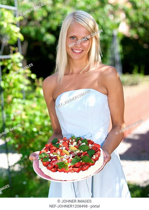 Woman holding cake in garden, close-up