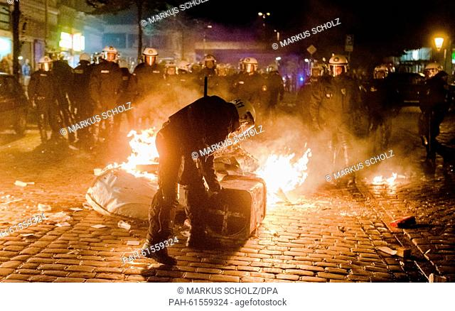 Riot police try to remove burning obstacles from a street during riots at Hamburg's Schanzenviertel district in Hamburg, Germany, 12 September 2015