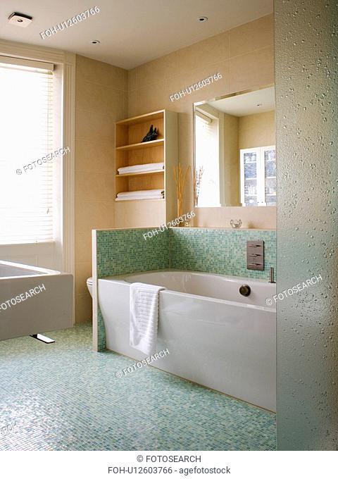 Green mosaic tiled floor and splashback above white bath in modern bathroom