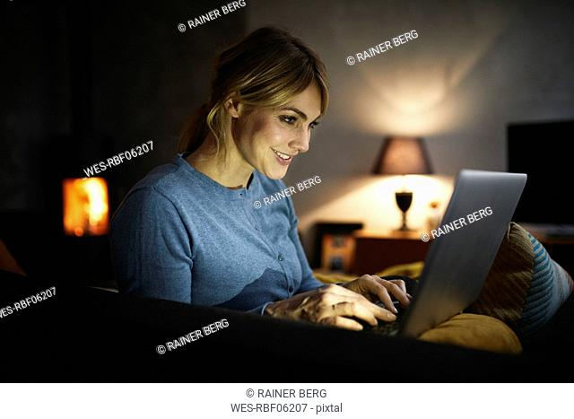 Smiling woman using laptop at home in the evening