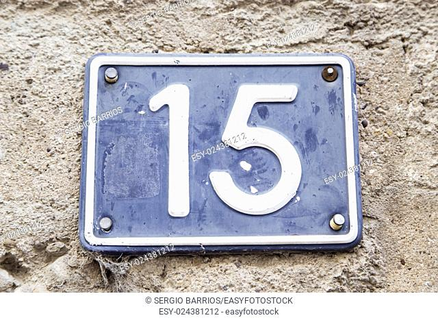 Number fifteen in a wall of a house, detail of a number of information, odd number