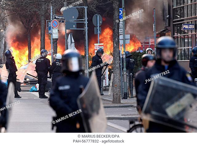 Riot police secure the area around a burning marked police vehicle prior to the opening of the new European Central Bank (ECB) headquarter inFrankfurt, Germany