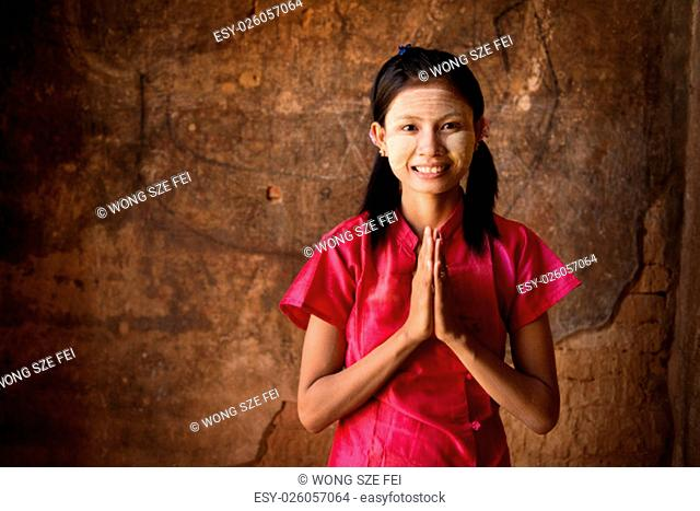 Young Myanmar woman in a traditional welcoming gesture