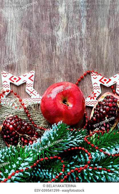 Pomegranate, apple with festive decorations over wooden background, selective focus, copy space