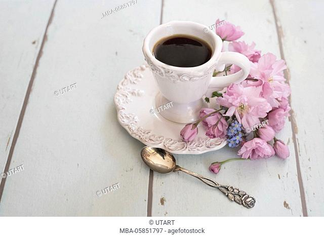 Flower arrangement with coffee cup in white, coffee, silver small coffee spoon and forget-me-not on vintage woodwork background, from above