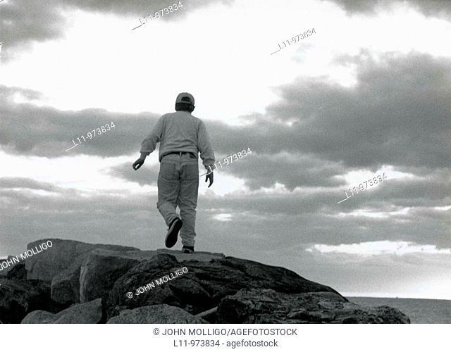 Boy on rocks, walking off towards clouds