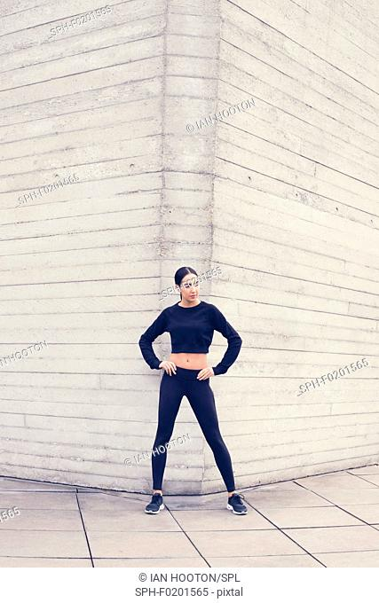 Woman by building with hands on hips