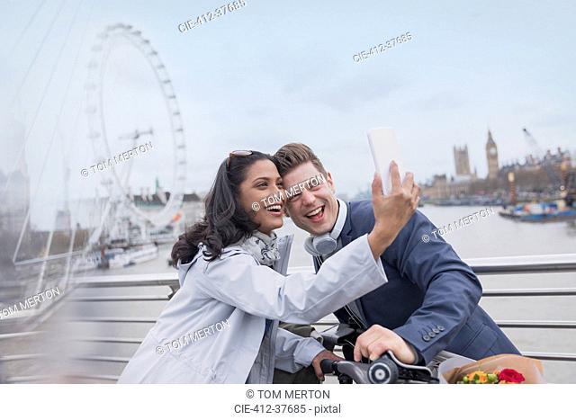 Smiling couple tourists taking selfie with camera phone on bridge near Millennium Wheel, London, UK