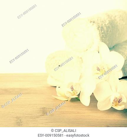 Spa set of white orchid flower and rolled towel on wood background, vintage style, closeup