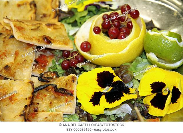 Pizza with onion, redcurrant and a pansy