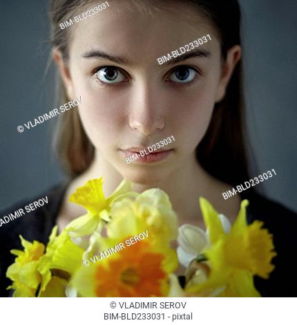 Caucasian girl holding yellow flowers