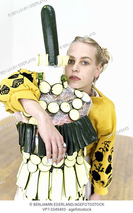 young woman with artistic fashion dress made of raw zucchini