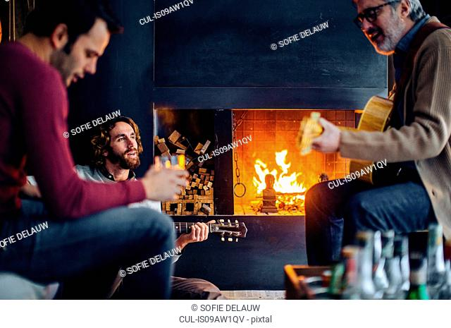 Mature man and adult sons playing guitars by living room fire