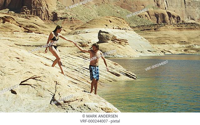 WS PAN Young couple jumping from rocky shore into Lake Powell / Utah, USA