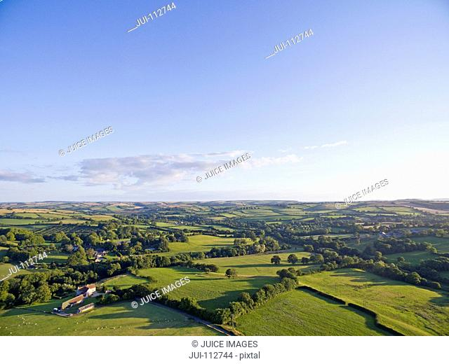 Scenic aerial landscape view of green fields in sunny rural countryside under blue sky