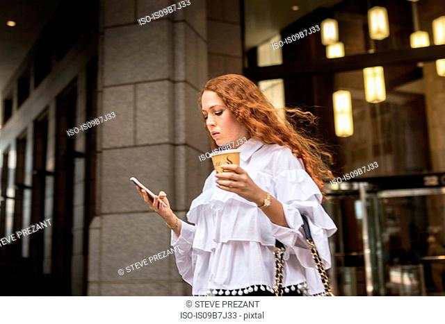Young businesswoman with takeaway coffee looking at smartphone on sidewalk, New York, USA