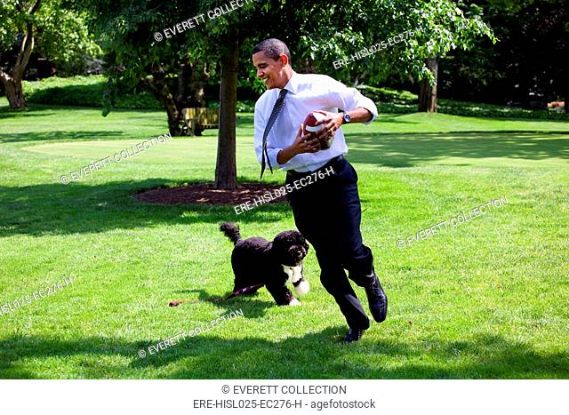 President Barack Obama runs away from the family dog Bo during a brief break from meetings on the South Lawn of the White House. May 12 2009