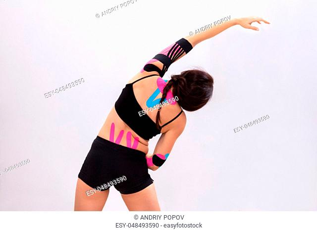 Close-up Of Woman Stretching Arms With Physio Tape On Her Back