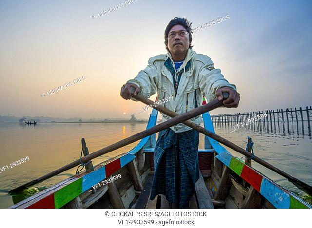 Amarapura, Mandalay region, Myanmar. Man rowing on his colorful boat on the Taungthaman lake at sunrise, with the U Bein bridge in the background