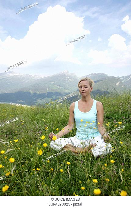 Woman practicing yoga, Kleinwalsertal, Allgau, Germany