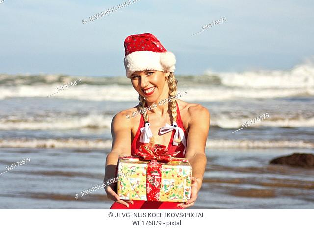 Santa girl in Santa hat with Christmas gift on the beach