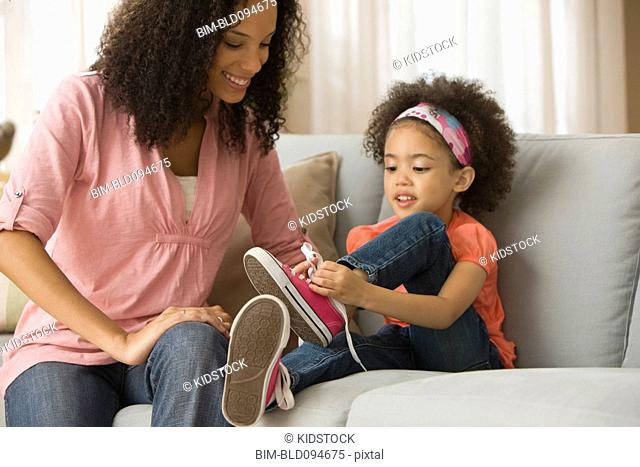 Mixed race mother putting on daughter's shoes