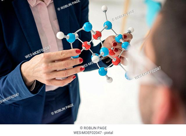 Businesswoman holding molecule model, teaching teenage boy