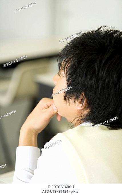 Teenage boy sitting at desk in classroom