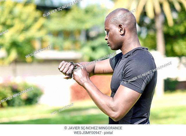 Runner checking smart watch fitness tracker