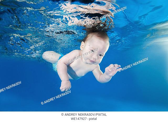5 months infant boy learning to swim underwater in waterbaby class in the pool