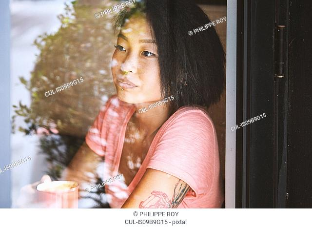 Woman gazing in cafe window seat, Shanghai French Concession, Shanghai, China