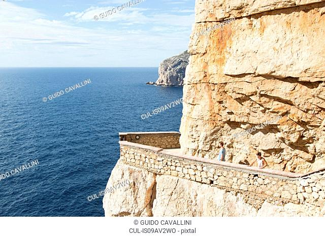 High angle view of young men by ocean on balcony carved into cliff, Grotta di nettuno (Neptune's Grotto), Capo Caccia,Sardinia,Italia