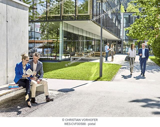Smiling colleagues with book sitting on bench outside office building