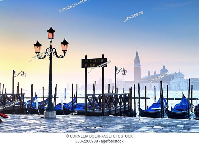 Gondolas moored on Grand Canal and Church of San Giorgio Maggiore beyond at sunrise, near Piazza San Marco, Venice, Veneto, Italy, Europe
